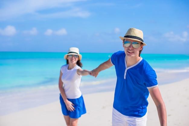 Família feliz se divertir em férias na praia do caribe