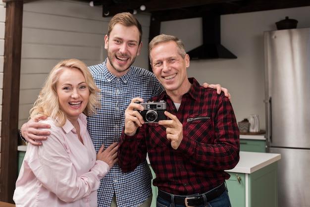 Família feliz, segurando a câmera na cozinha