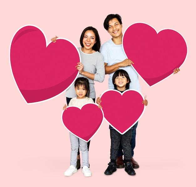 Família feliz segurando formas de coração