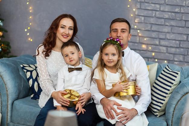 Família feliz, segurando o presente de natal, olhando para a câmera