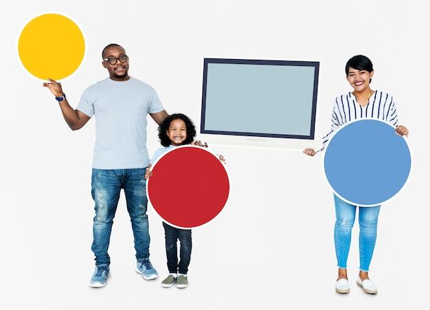 Família feliz segurando placas redondas e uma tela