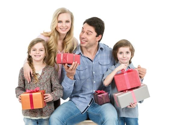 Família feliz segurando presentes isolados no fundo branco. conceito de férias e venda.