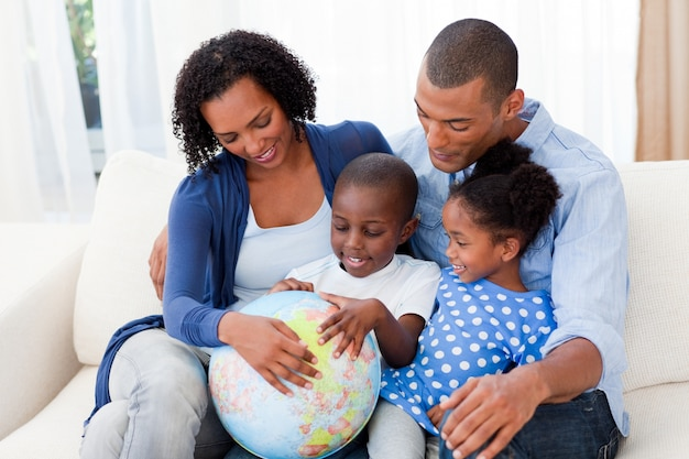 Família feliz segurando um globo terrestre