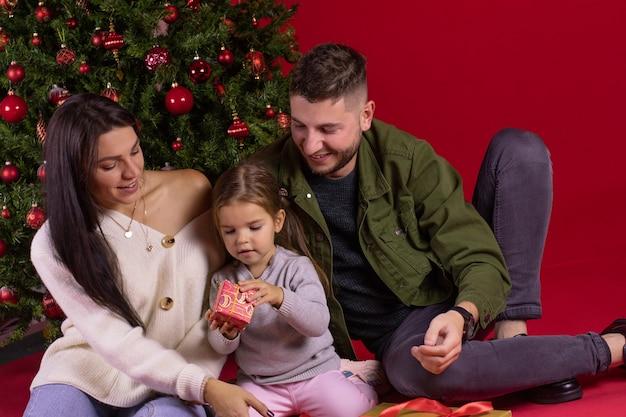 Família feliz sentada ao lado de uma árvore de natal