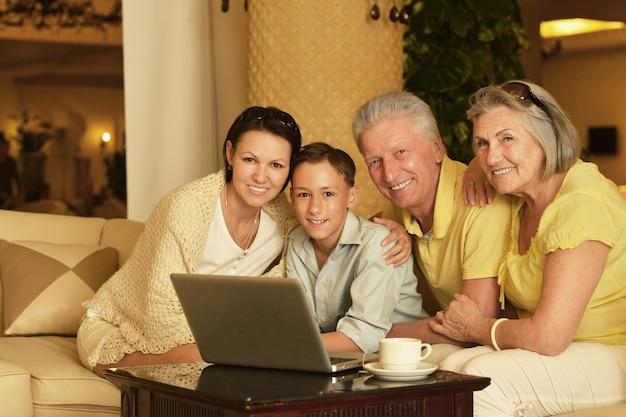 Família feliz sentada com laptop e tablet na mesa