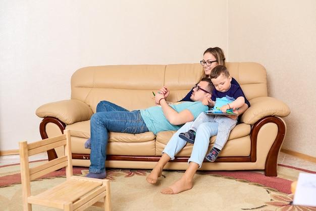 Família feliz sentada com um tablet na sala no sofá