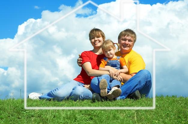 Família feliz sentada em casa na grama verde sob o céu com nuvens