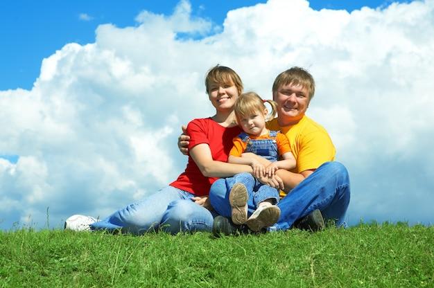 Família feliz sentada na grama verde sob o céu com nuvens