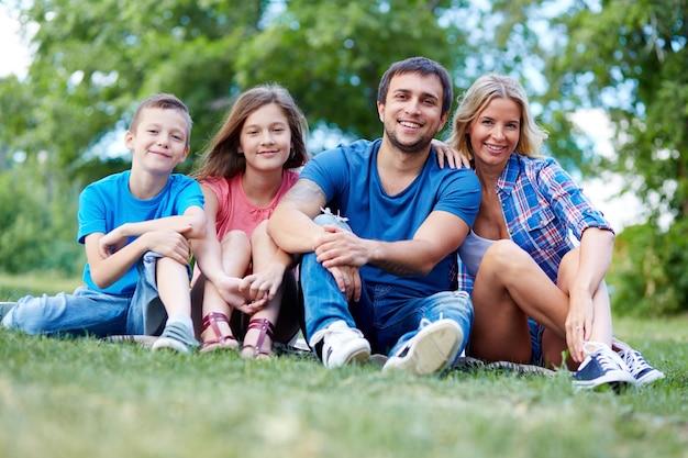 Família feliz sentada na grama