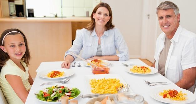 Família feliz sentada na mesa de jantar