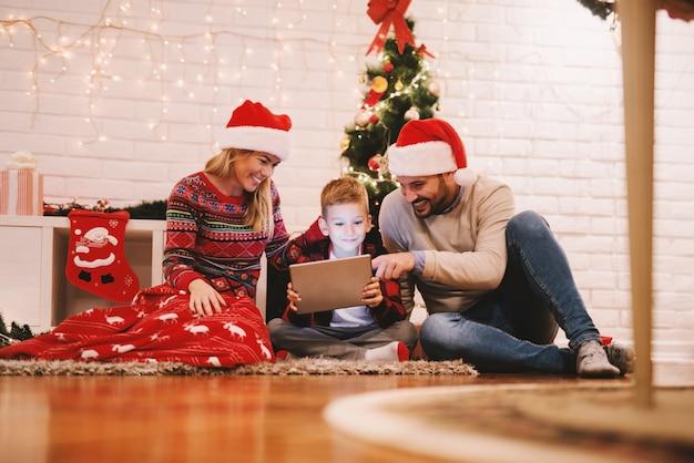 Família feliz sentada no chão em frente à árvore de natal e assistindo vídeos no tablet.