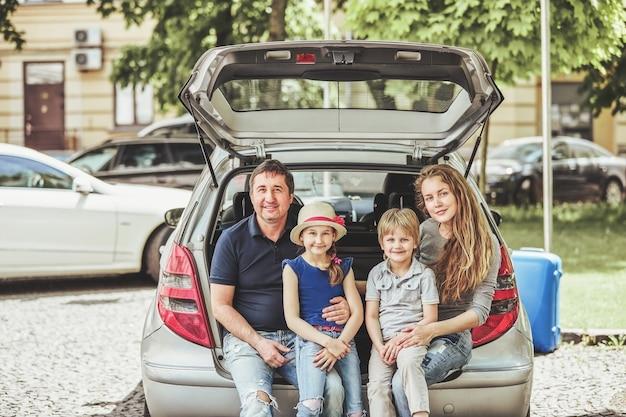 Família feliz sentada no porta-malas de um carro familiar. o conceito de viagens em família