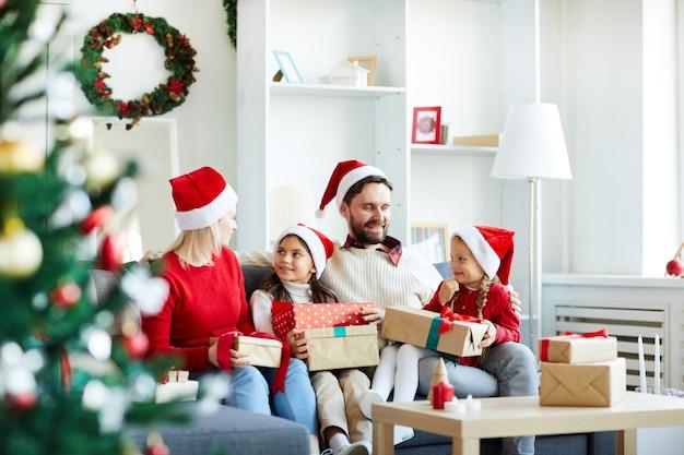 Família feliz sentada no sofá desembrulhando presentes de natal
