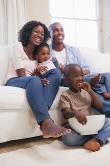 Família feliz sentada no sofá juntos assistindo tv