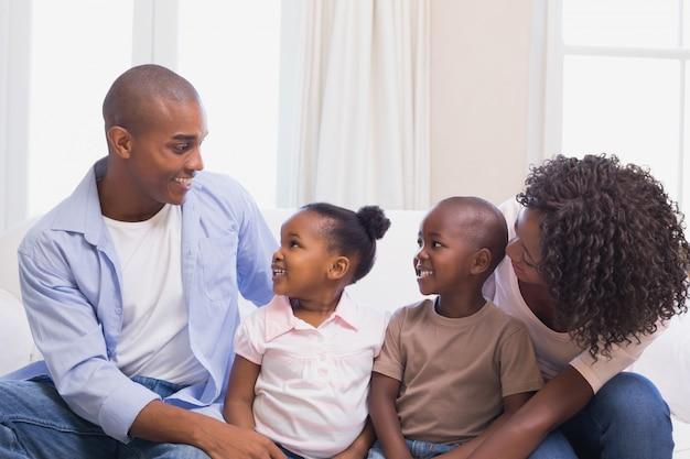Família feliz sentada no sofá juntos