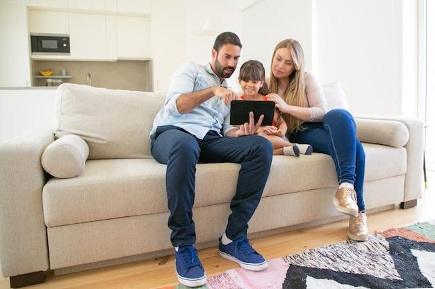 Família feliz sentada no sofá, usando o aplicativo online do tablet, olhando para a tela, assistindo filme juntos.