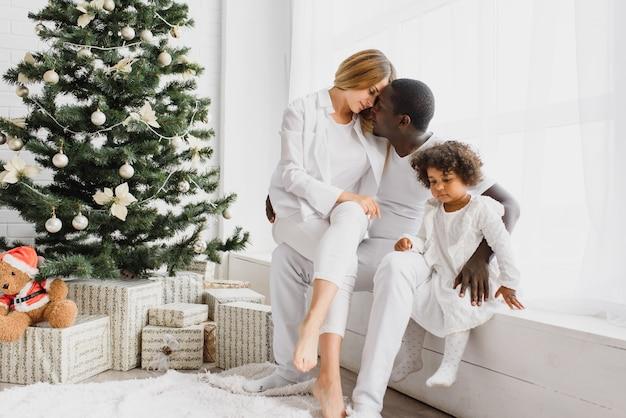 Família feliz sentada perto da árvore de natal