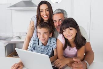 Família feliz sentado na cozinha usando seu laptop