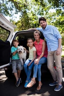 Família feliz sentado na mala do carro com seu cachorro