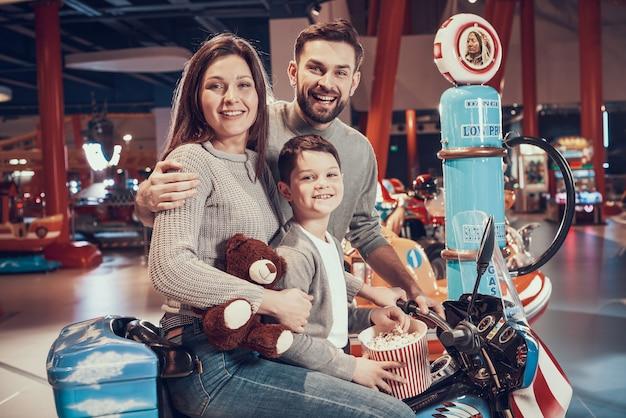 Família feliz sentado na moto de brinquedo com pipoca.