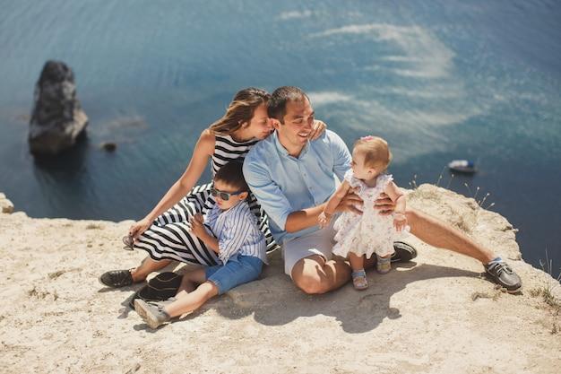Família feliz sentado nas montanhas à beira-mar