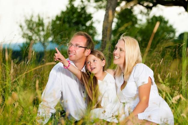 Família feliz sentado no prado