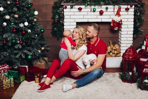 Família feliz sentado perto da lareira com o filho pequeno e cachorro fofo e sorrindo