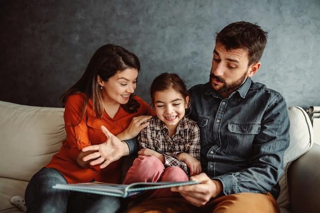 Família feliz sentados juntos e tendo bons momentos juntos. o pai está lendo um conto de fadas para sua filha amada.