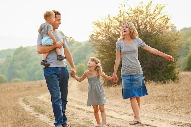 Família feliz sobre a natureza das crianças repousa com o fundo da estrada