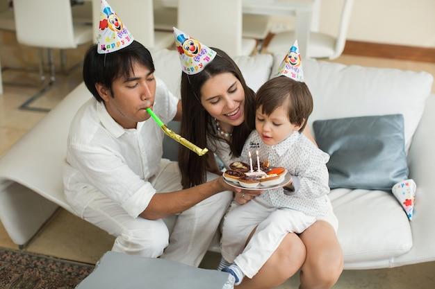 Família feliz, soprando velas juntos para um aniversário em casa