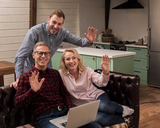 Família feliz sorrindo e acenando na cozinha