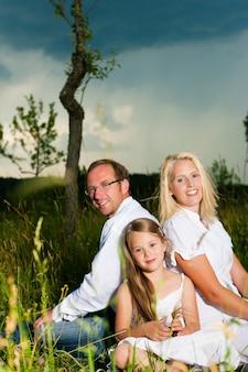 Família feliz sorrindo na frente da tempestade que se aproxima