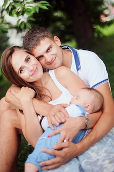 Família feliz. sorrindo pais com criança. pai considerável e mãe nova que guardam a filha pequena no parque. linda mulher e homem sentado na grama com o bebê.