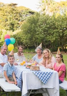 Família feliz sorrindo para a câmera na festa de aniversário