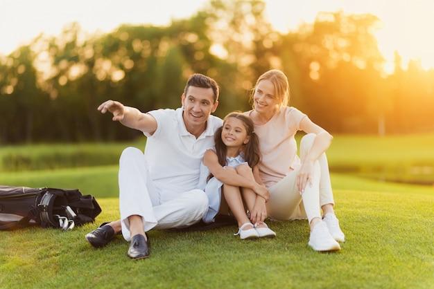 Família feliz tem descanso depois de golfe em um curso.