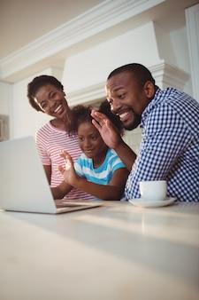 Família feliz, tendo uma chamada de vídeo no laptop
