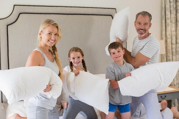 Família feliz, tendo uma luta de almofadas no quarto