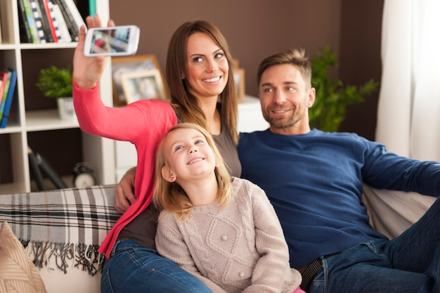 Família feliz tirando selfie em casa