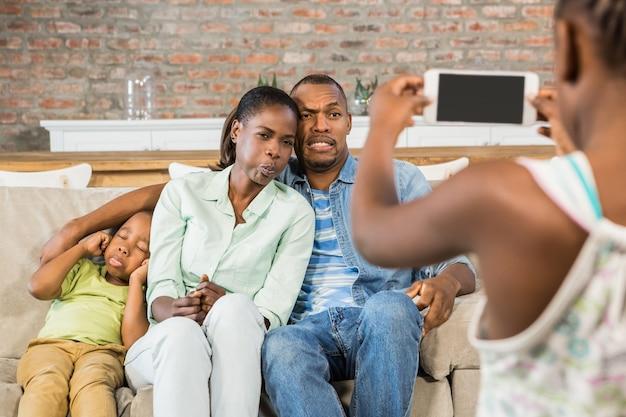 Família feliz tirando uma foto no sofá na sala de estar