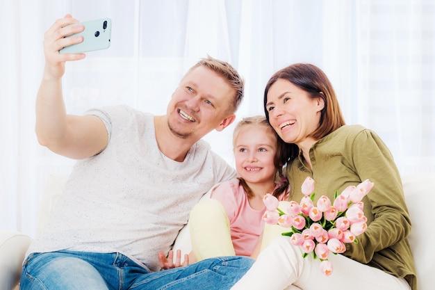 Família feliz tirando uma selfie com presentes festivos no dia das mães