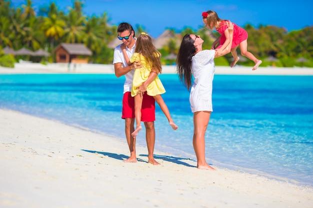 Família feliz tocando juntos na praia branca