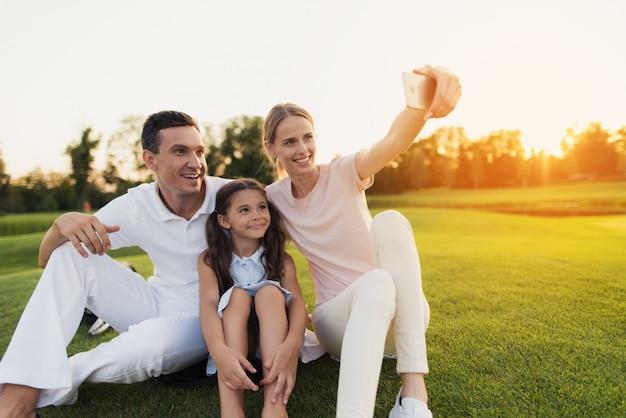 Família feliz toma selfie sentado no gramado verde.