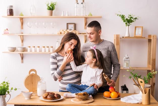 Família feliz tomando café da manhã com torradas na cozinha