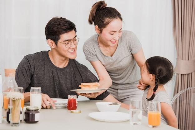 Família feliz tomando café da manhã em casa