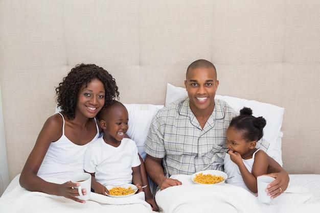 Família feliz tomando café da manhã na cama juntos pela manhã