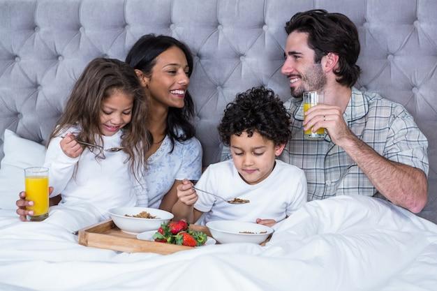 Família feliz tomando café da manhã na cama
