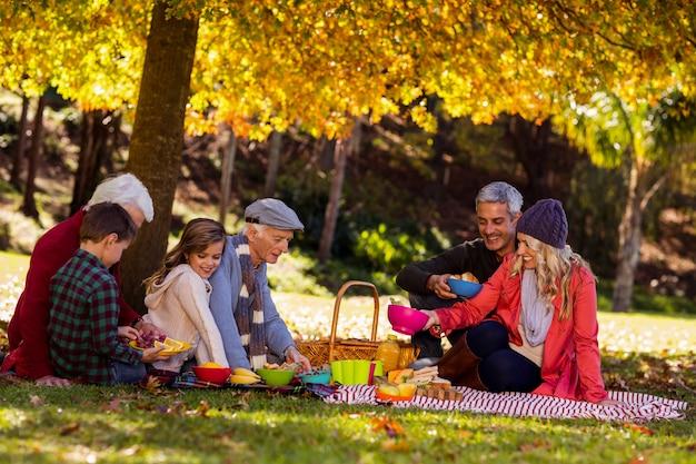 Família feliz tomando café da manhã no parque