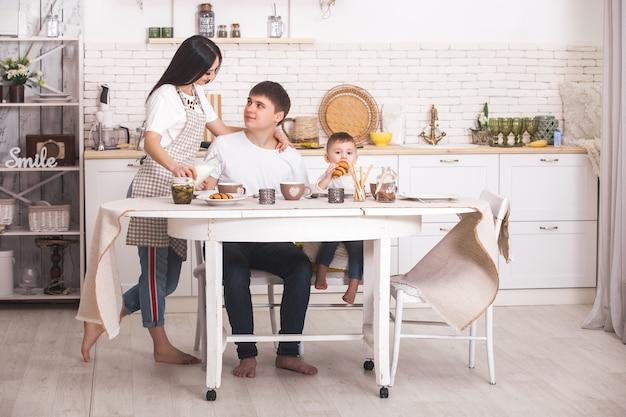 Família feliz tomando café juntos. família jovem comendo à mesa na cozinha. mãe, pai e bebê comendo.
