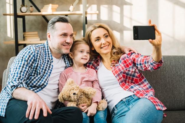 Família feliz tomando selfie no sofá