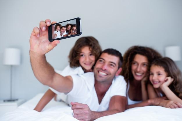 Família feliz tomando uma selfie na cama